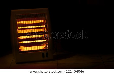 Electric heater with halogen coils in darkness - stock photo