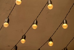 electric incandescent bulbs with warm yellow light hang in chains from the ceiling. bottom view. blurred background