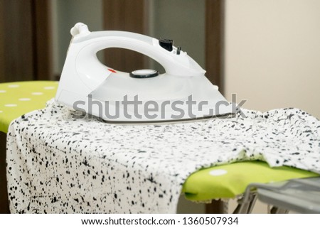 Electric iron and t-shirt on ironing board in room #1360507934