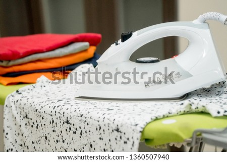 Electric iron and t-shirt on ironing board in room #1360507940
