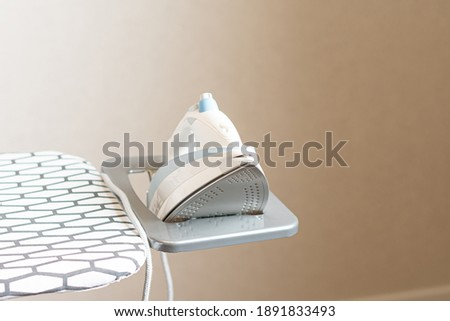 Electric iron on ironing board Photo stock ©