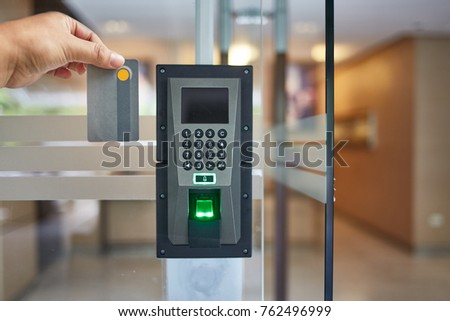 Electric key card and finger scan controls systems for building. Hand holding a key card for unlocking the door