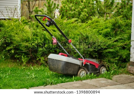 Electric lawn mower on the background of the lawn #1398800894