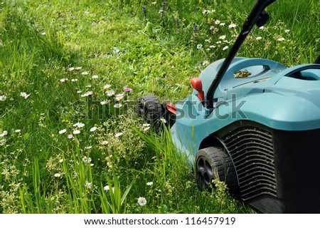 electric lawn mowers running on green - stock photo