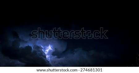 Electric Lightning bolt inside a thunderhead of dark blue clouds at night