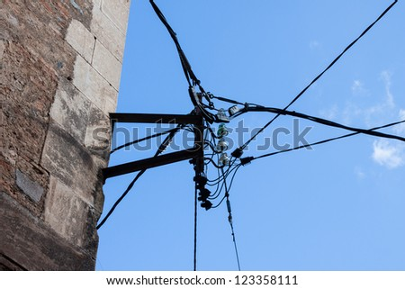 Electric line on the ancient house wall of spanish city.