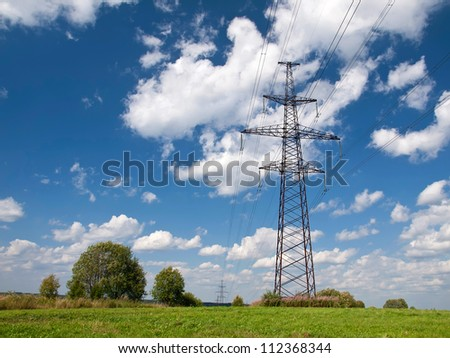 Electric main against the sky with clouds on a green meadow.