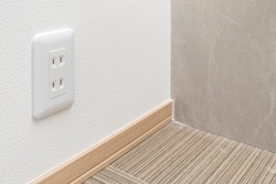 Electric outlet on white wall.