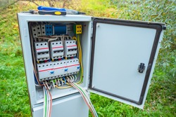 Electric panel on the street. Metal cabinet with electrical switches. Electric cabinet on background grass. Electrification cabinet. Concept for electrification of suburban housing. Electrical setup