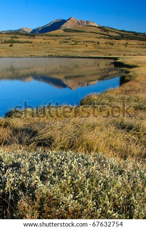 Electric Peak reflects in the blue water of Swan Lake.  Yellowstone National Park. - stock photo