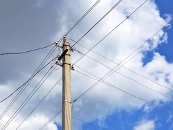 Electric pole and intersecting wires on a background of blue sky and clouds. Illustration on the theme of electricity transportation, electrification of the countryside, rising energy prices