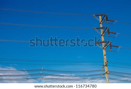electric pole near a pond on a background of blue sky - stock photo