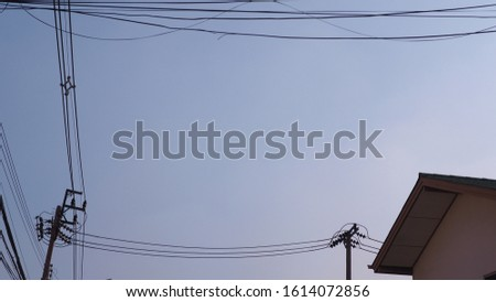 electric pole, power pole, house roof and clear blue sky background.