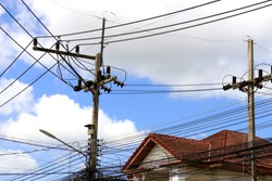 electric pole with blue sky background and Red house roof