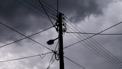 Electric pole with lightning rod against the stormy sky