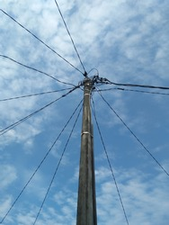 Electric poles with interconnected wires against a white cloudy blue sky in the countryside. Wired network, tall, and complicated