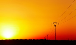 Electric power line in Sahara Desert against colorful sky at sunset