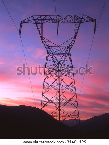 Electric power lines and tower photographed at sunset.