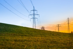 Electric power lines at sunset with green grass in foreground