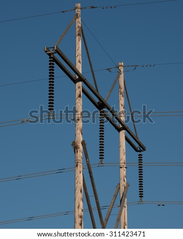 Electric power lines mounted on insulators and a tall wood power pole.  These wire transfer electrical energy to households and industry.