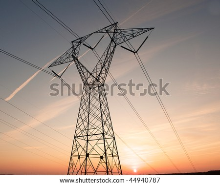 Electric power pylon and wires silhouetted by ab colorful sunset.