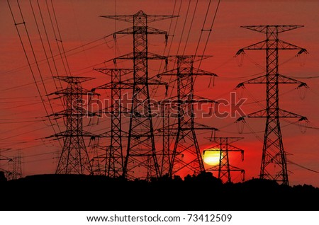 Electric power pylon congested on a hill against a surreal bloody red sunset.