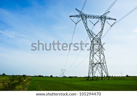 Electric power station in the field in blue cloudy sky