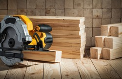 electric power tool corded circular hand saw on wooden background