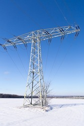 Electric power tower pole or pylon in winter snow covered landscape background with blue sky