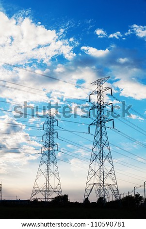 Electric power towers in blue sky before Sun set