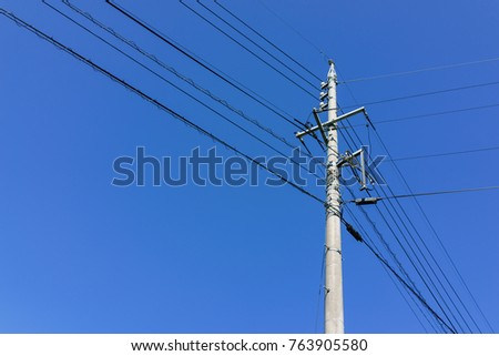 Electric powerline with pole and wire with clear blue sky background. #763905580