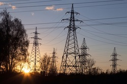 Electric powerlines. High voltage power lines, pylons over sunrise with sun