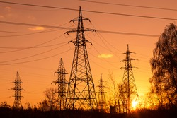 Electric powerlines. High voltage power lines, pylons over sunset orange red sky with sun