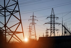 Electric powerlines on electric substation and distribution power. High voltage power lines, pylons at sunset