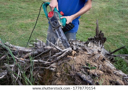 electric saw in action cutting wood. Man cutting wood with saw, dust and movements. Close-up of woodcutter sawing chain saw in motion, sawdust fly to sides.