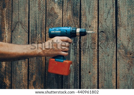 Electric screwdriver in hand at wooden desk background
