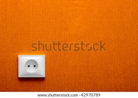 Electric socket in a orange wall in the corner