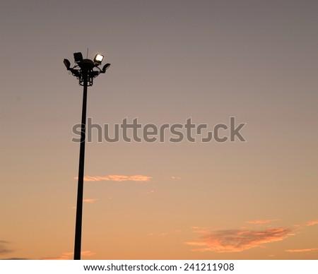 electric spotlight pole on sunset sky   #241211908