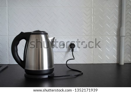 Electric stainless steel kettle on a granite counter top against a ceramic background Stock photo ©
