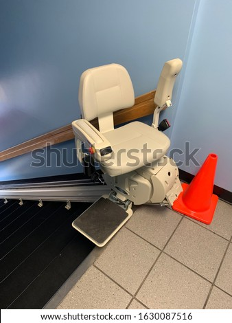 Electric stair chair lift at top of flight of stairs with pylon