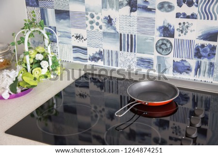 Electric stove. Frying pan is placed on a modern electric stove, black induction stove, cooker, hob or built in cooktop with ceramic top in Luxury kitchen interior .