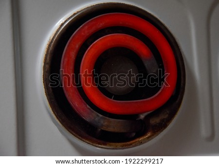 Electric stove, hot spiral at the stove. Bright red spiral curls side view. Red hot, glowing element. Electric stove with a spiral. Heating element on an electric stove. view from above