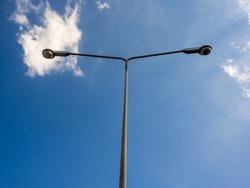Electric street light pole on blue vivid sky in day light.