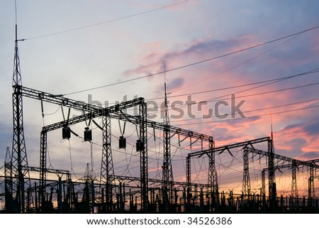 Electric substation on a background of the coming sun - stock photo