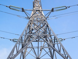 Electric support, illuminated by the bright sun.Metal support for high voltage power lines against the sky. Electrical cables are attached to the pylon on poles through glass insulators. Electrical in