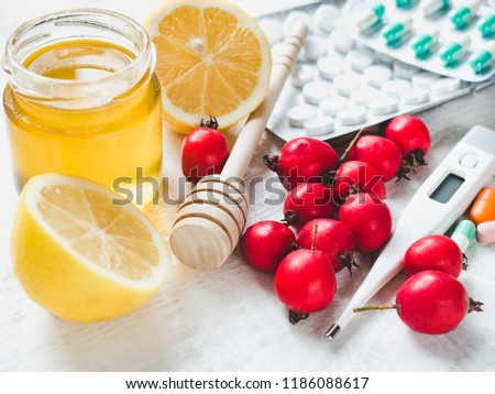Electric thermometer, pills, fresh yellow lemon, jug of honey and red berries on a white wooden table. Top view, close-up, isolated. Concept of preventing colds #1186088617