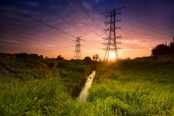Electric tower at sunset with sun.