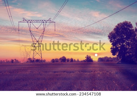Electric towers on a field with sunrise.