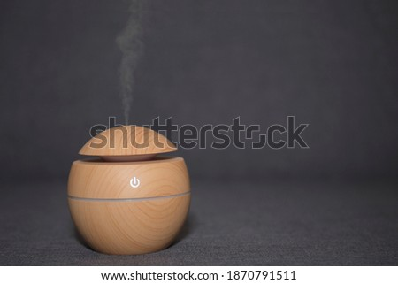 Electric ultrasonic humidifier emitting atomized water droplets on a dark background. The device is round in shape with a wooden body. Stok fotoğraf ©