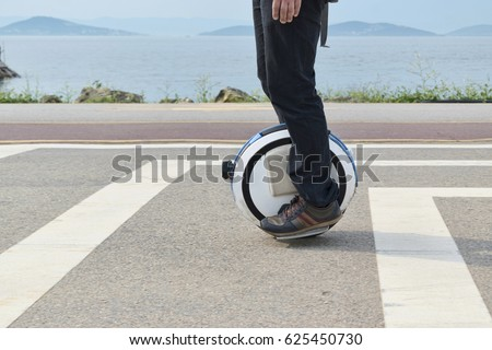 electric unicycle. a man rides...
